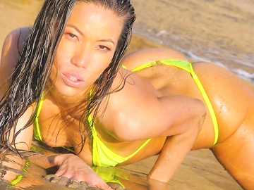 Kalina Ryu seductively flaunts her shaved pussy in oil on the sea shore